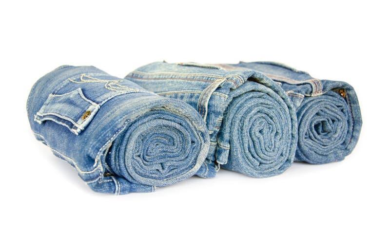 滚动被安排的蓝色牛仔布牛仔裤在白色背景 图库摄影
