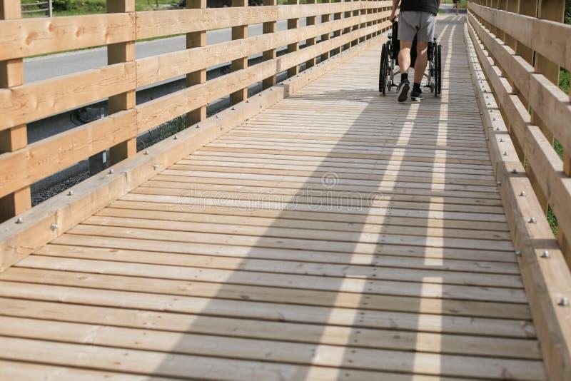 助理和残疾年轻人轮椅的 图库摄影