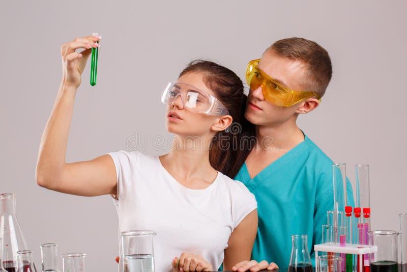 助理,考虑有绿色液体的一个烧瓶 户内实验室 隔离 免版税库存图片