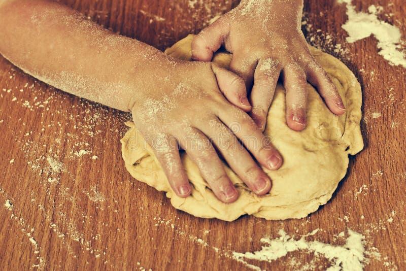 努力儿童手做面团。 免版税图库摄影