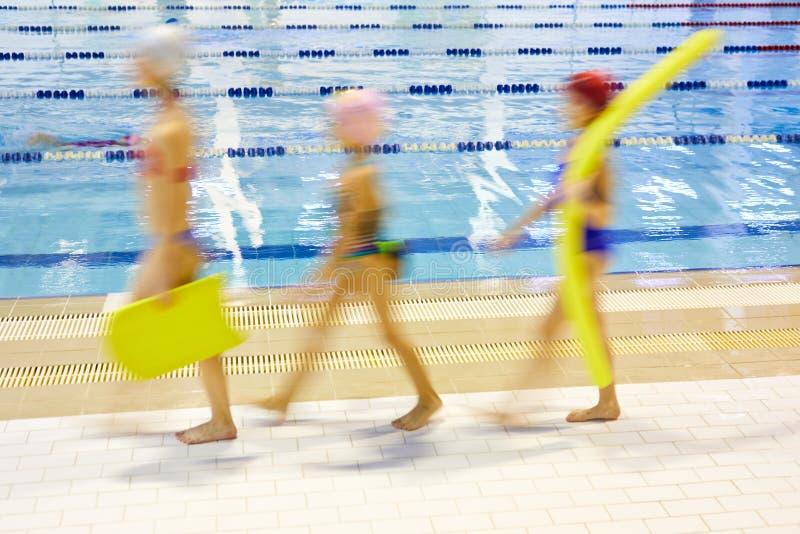 努力去做在游泳教训的孩子 库存照片