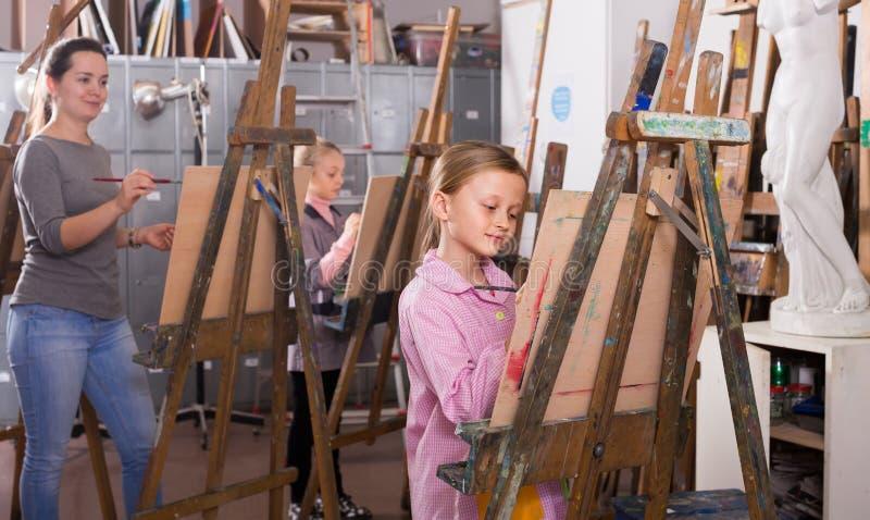努力地训练他们的绘画技能的女小学生在cla期间 库存图片