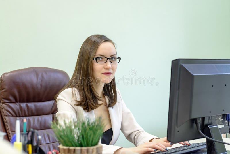 努力工作在书桌的年轻女商人在研究,经济学家会计财务报表中,核实docum的准确性 免版税图库摄影