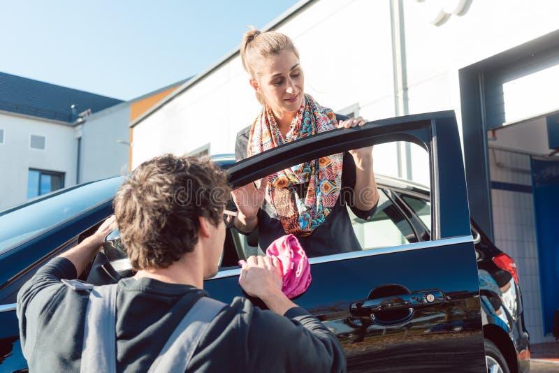 努力清洗她的在商业洗涤的服务人帮助的妇女汽车 库存照片