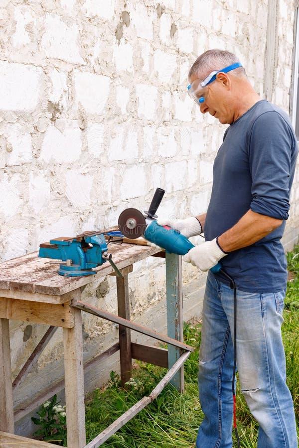 努力高效率的严肃的高兴的工作者在房子后院进行与电工具的修理锤击和钳子 免版税图库摄影