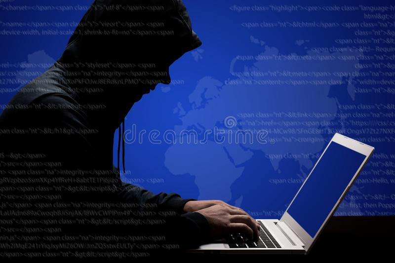 努力黑hoody工作的危险男性黑客在解决在便携式计算机上的网上密码代码,键盘信息,尝试t 免版税库存照片