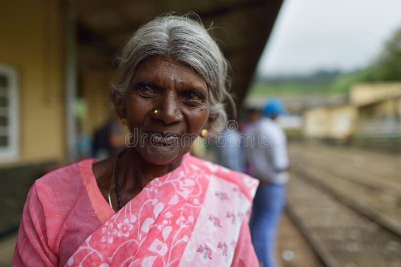 努沃勒埃利耶,斯里兰卡, 2015年11月13日:等待在努沃勒埃利耶的火车站的老妇人火车 库存照片