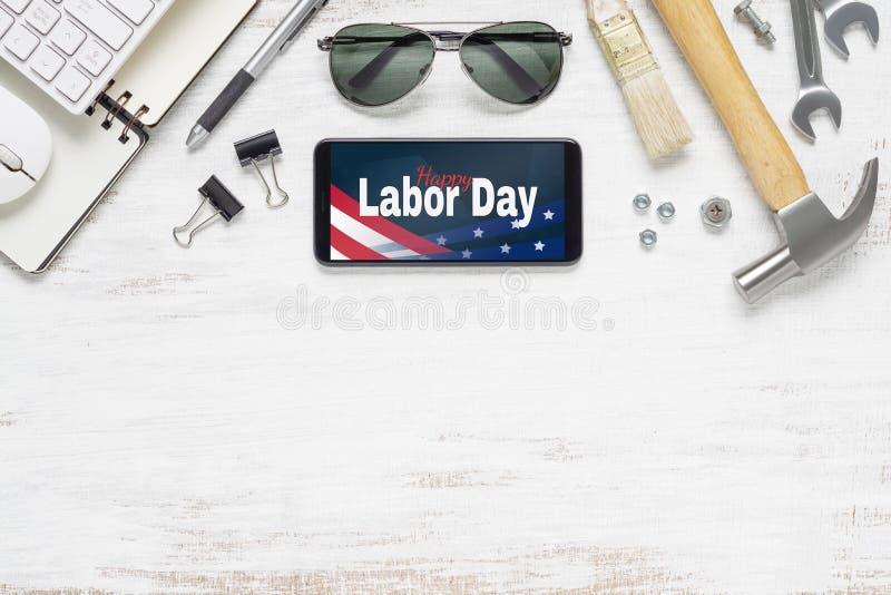 劳动节摘要背景概念台式视图  平被放置的大模型智能手机与愉快的劳动节美国假日和根本 免版税库存照片