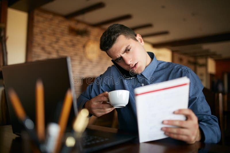 劳累过度的商人发表演讲关于举行它的手机与肩膀,读在笔记本的文字,饮用的咖啡和 库存图片