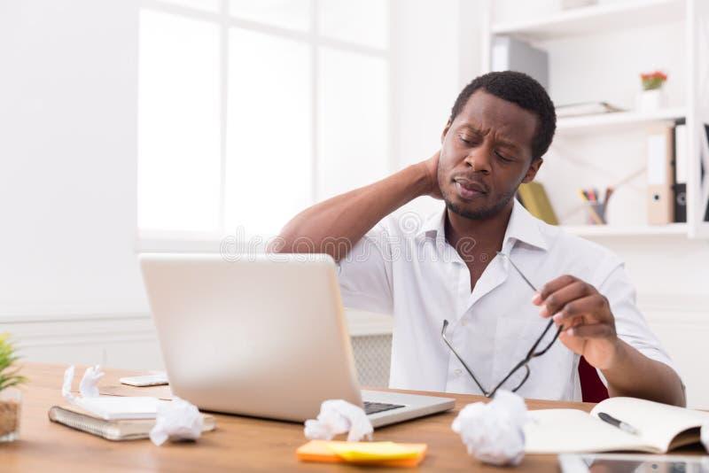 劳累过度的非裔美国人的雇员在办公室,与膝上型计算机一起使用 免版税库存照片