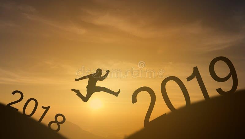 勇敢的人成功的概念,跳过太阳的剪影人在山的空白之间从2018年到2019个新年,它感受 免版税库存照片