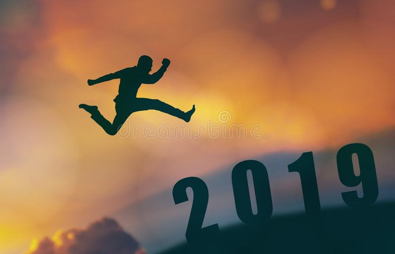 2019勇敢的人成功的概念,跳过太阳的剪影人在山的空白之间到2019个新年,感觉象wi 免版税库存照片