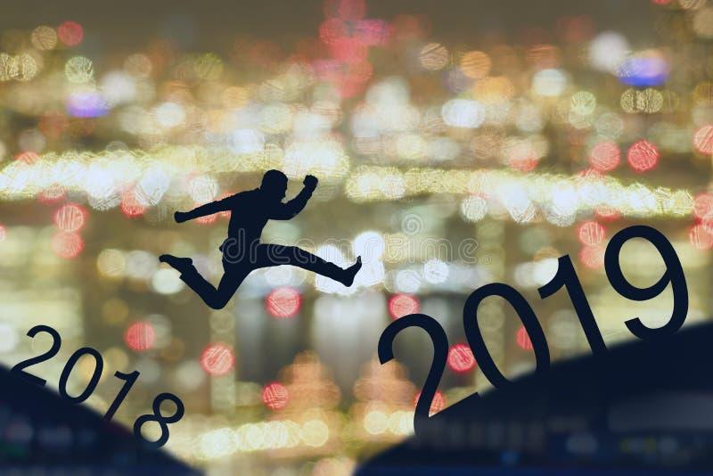 2019勇敢的人成功的概念,跳过空白的剪影人在大厦,城市scape,风景之间对2019个新年,感受l 免版税库存照片
