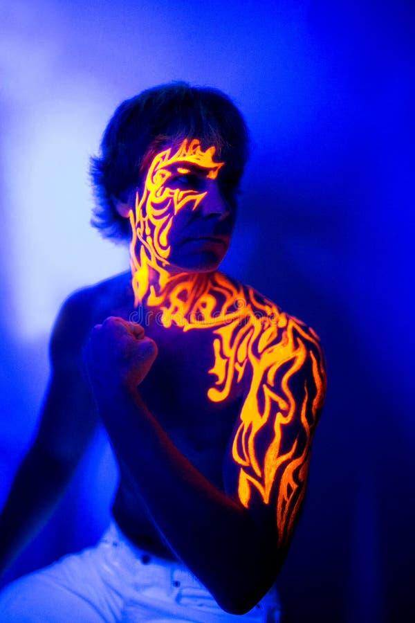 勇敢的人紫外画象霓虹面孔艺术,明亮的火能量 库存图片