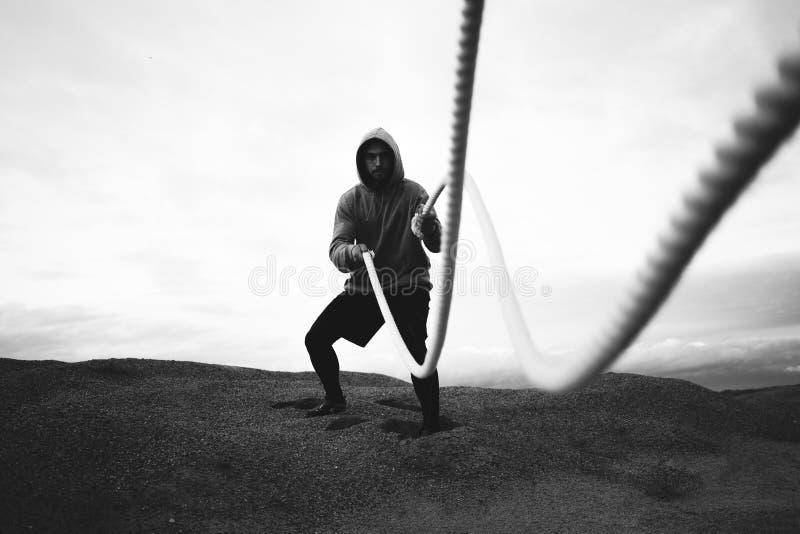 勇敢的做intens锻炼的运动员佩带的运动服使用在室外的争斗绳索 免版税库存图片