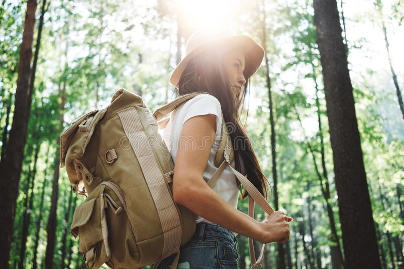 勇敢的单独旅行在树中的行家妇女佩带的背包和帽子在森林里户外 免版税库存图片