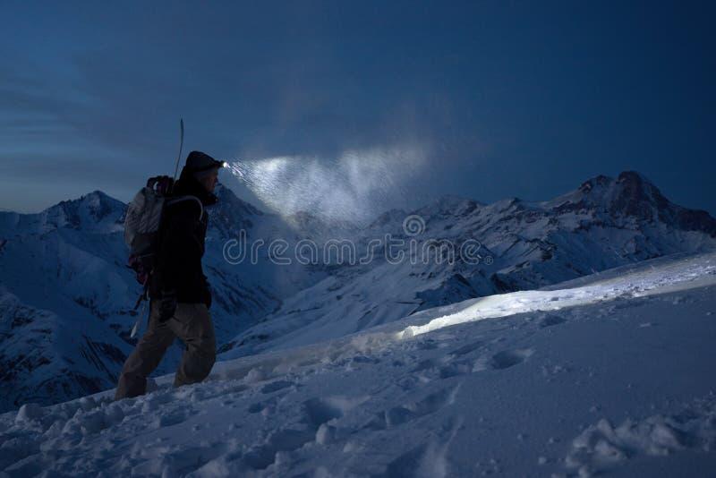 勇敢的夜探险家在高多雪的山上升并且点燃与前灯的方式 极端远征 滑雪游览 挡雪板 免版税库存图片