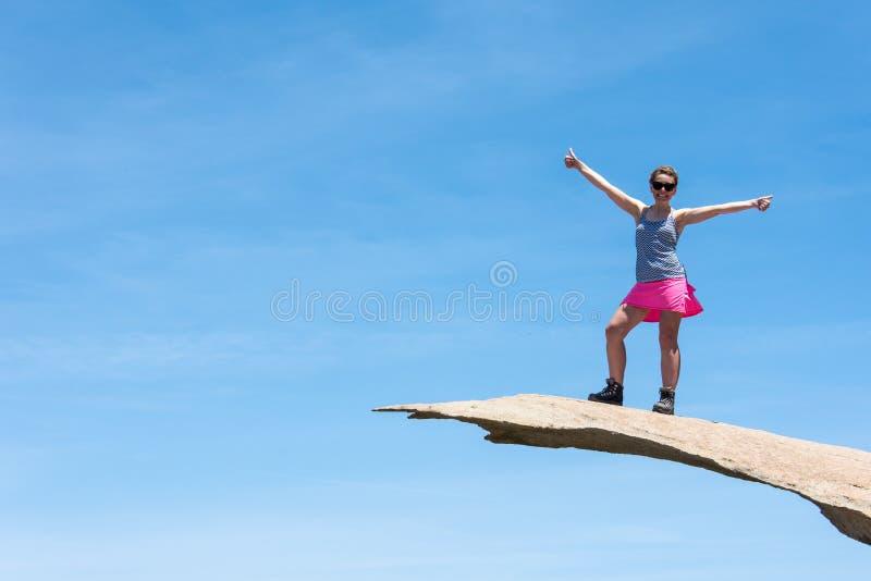 勇敢的年轻妇女徒步旅行者站立在薯片岩石顶部在圣迭戈加利福尼亚 库存图片