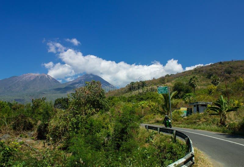 勒沃托比火山山风景,孪生火山,街道道路和摩托车从Larantuka,东部努沙登加拉群岛,印度尼西亚 库存照片