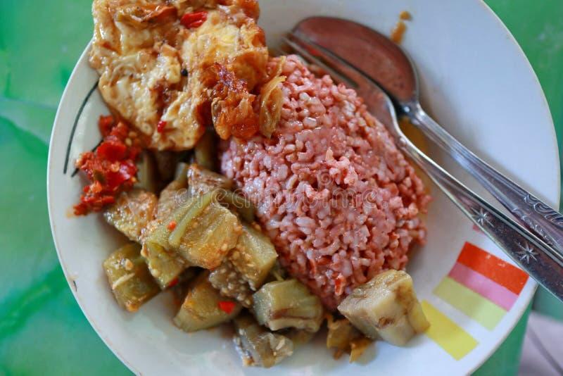 包含与茄子和蛋dishe的传统爪哇食物红色米 库存图片