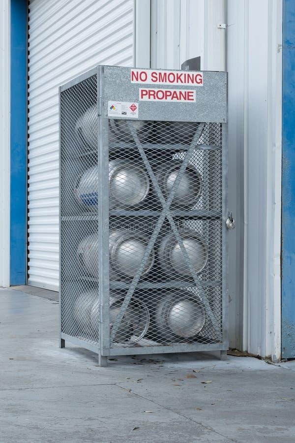 包含在大厦之外的被挂锁的钢笼子八个丙烷煤气罐 库存照片
