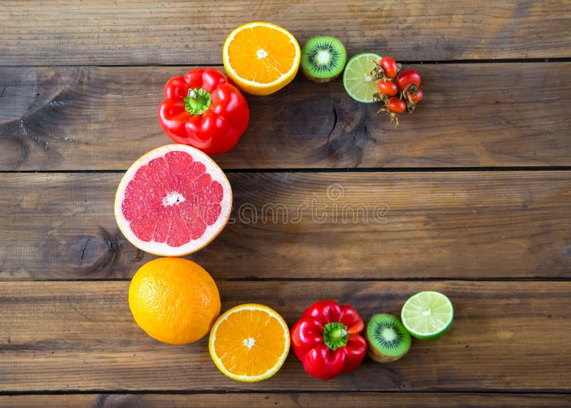 包含在木背景的产品维生素C 词C由水果和蔬菜做了浓在维生素C上 免版税库存照片