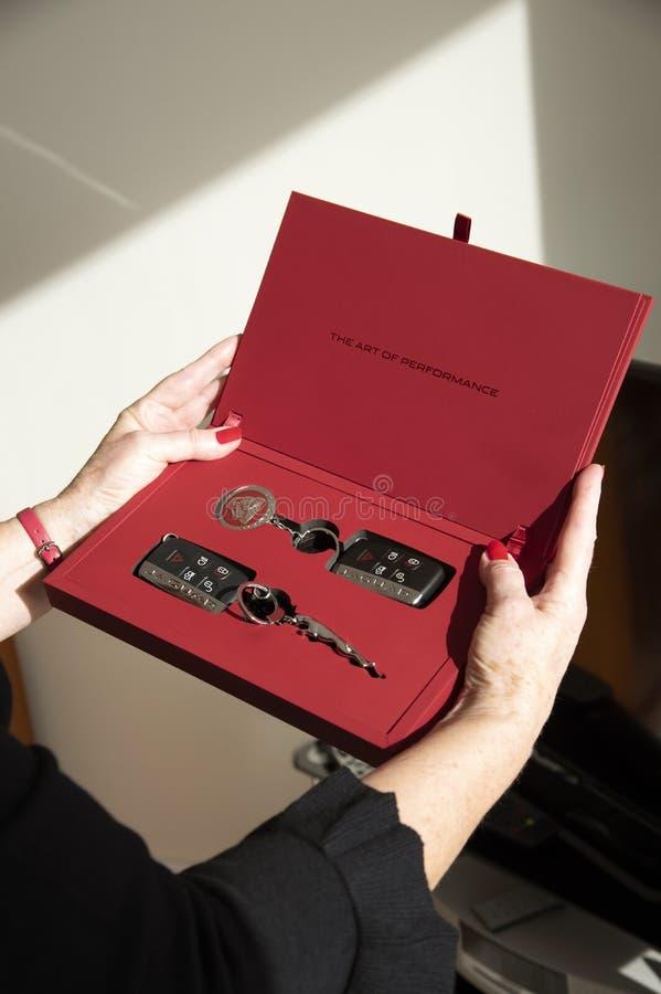 包含汽车钥匙和拍击声的红色赠送箱 库存照片