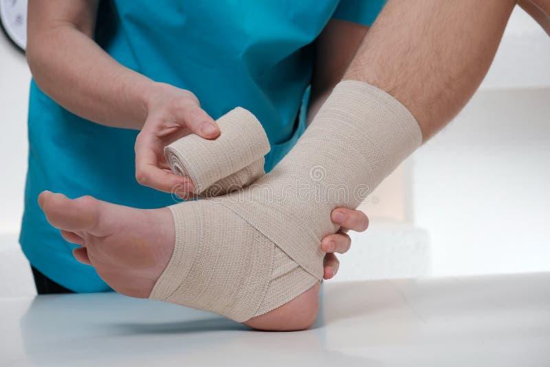 包扎女性患者的脚的男性医生特写镜头 免版税库存照片