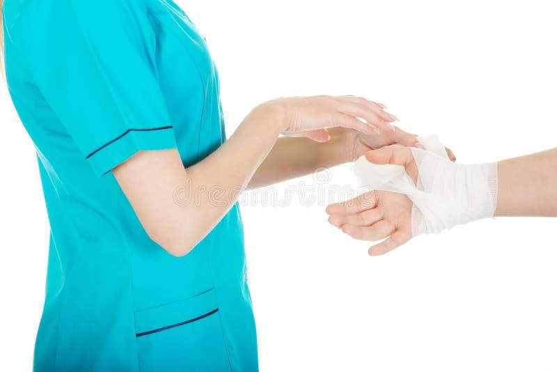 包扎女性手的妇女医生 免版税库存图片