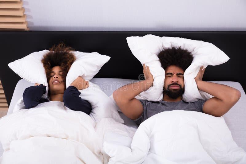 包括他们的耳朵的年轻夫妇用枕头 库存照片