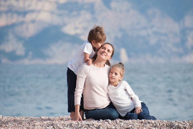 包括微笑的母亲和两个孩子的愉快的美丽的家庭亲吻她的在海海滩的开会在凉快的夏天日落天 库存图片