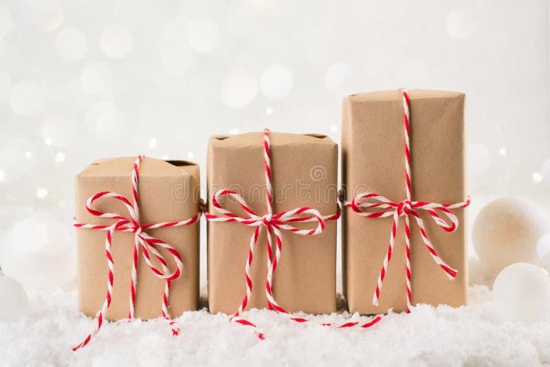 包装圣诞节礼物 在牛皮纸包裹的三个圣诞礼物箱子栓与在冬天背景的红色和白色串 图库摄影