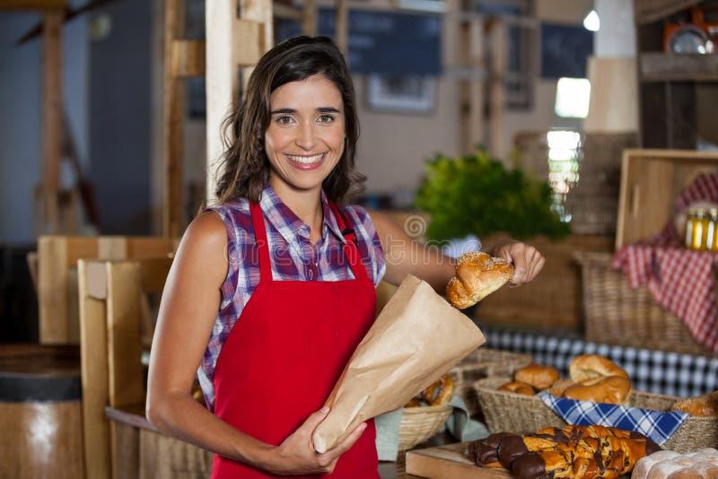 包装在纸袋的微笑的女职工甜食物在柜台在面包店商店 免版税库存图片
