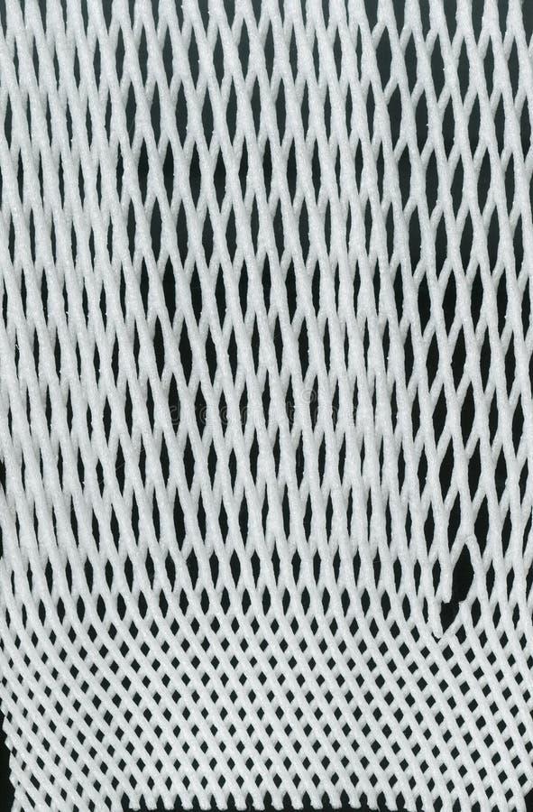 包装在黑背景的Textureof白色综合性滤网 尼龙白色宏观纹理样式背景 免版税库存照片