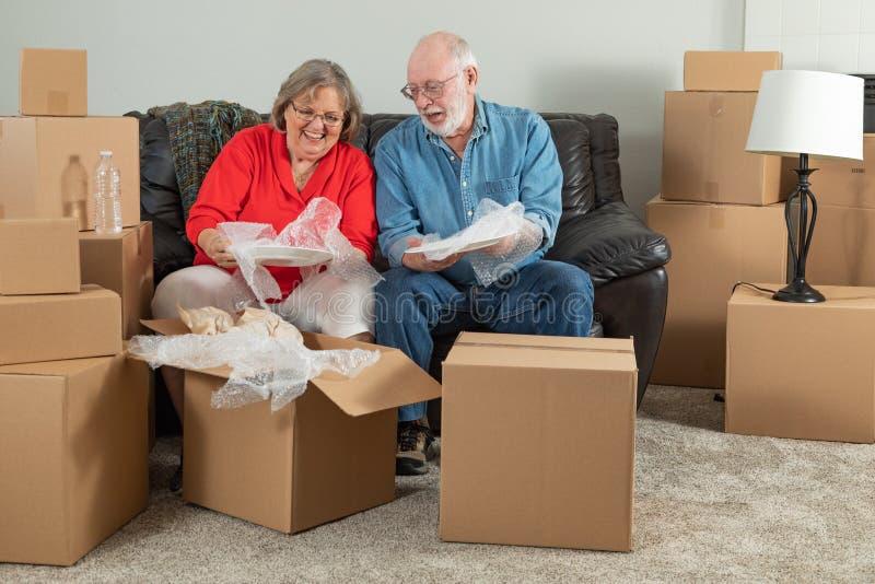 包装或打开移动的箱子的资深夫妇 库存照片