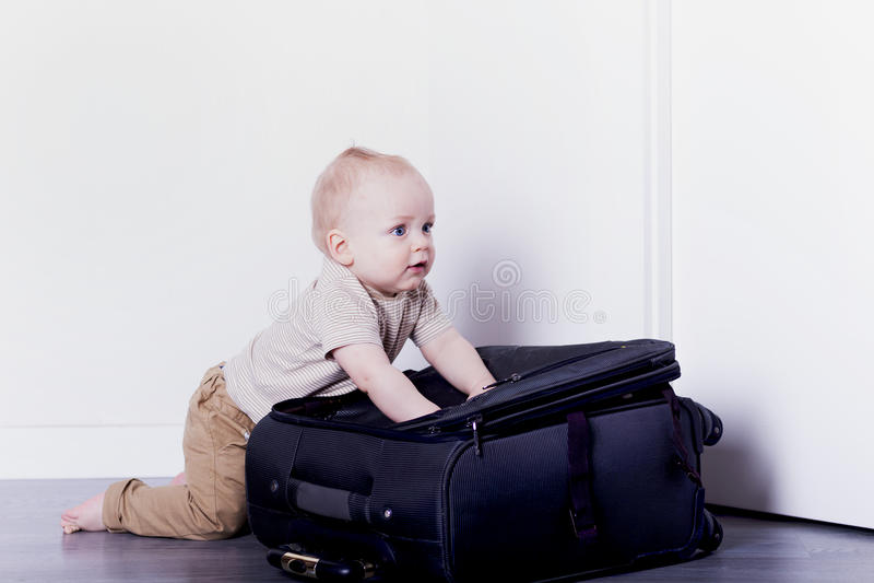 包装手提箱的婴儿男孩 去旅行的逗人喜爱的男婴 免版税库存照片