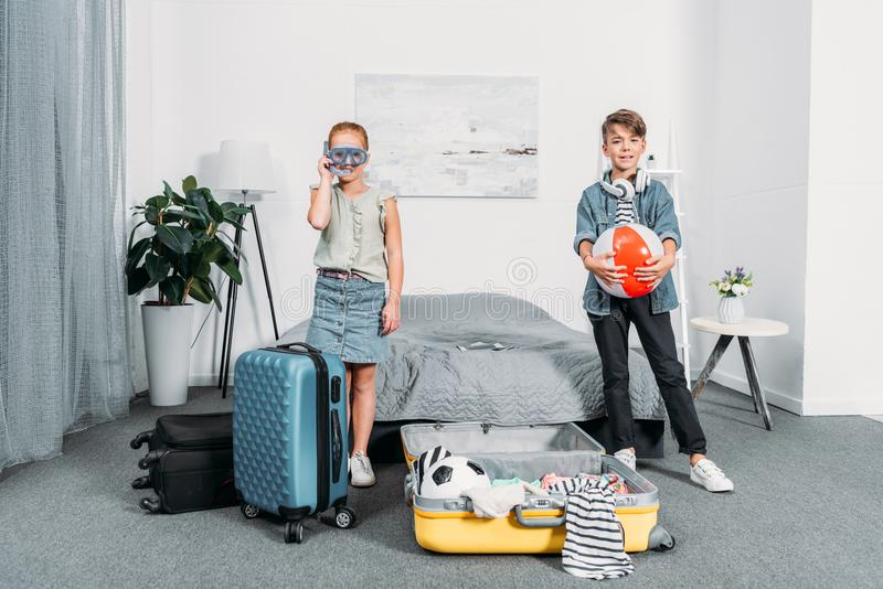 包装旅行的可爱的小孩衣裳 库存照片