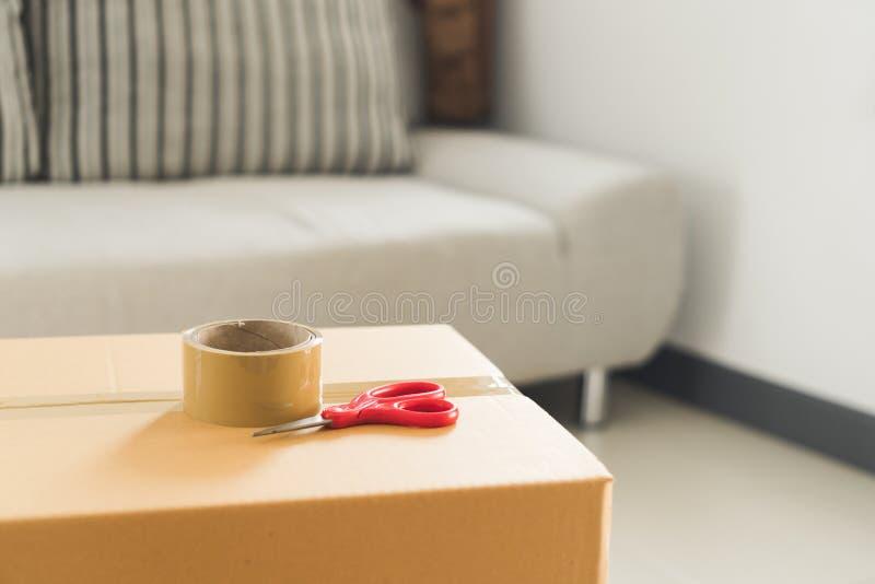 包装有透明胶带的纸板箱和红色在屋子里剪 免版税库存照片