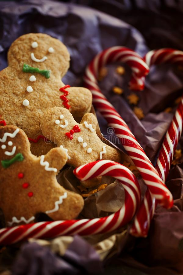 包装纸的微笑的姜饼人与棒棒糖特写镜头 在黑暗的背景的圣诞节曲奇饼 圣诞节礼品 库存图片