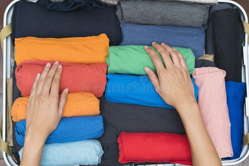 包装行李的妇女的手 免版税库存图片