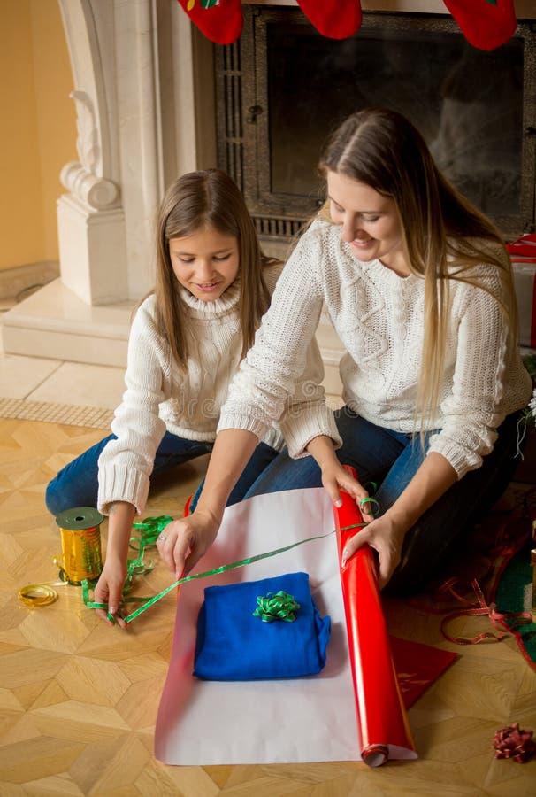 包裹与她的女儿的美丽的母亲圣诞节礼物 免版税库存照片