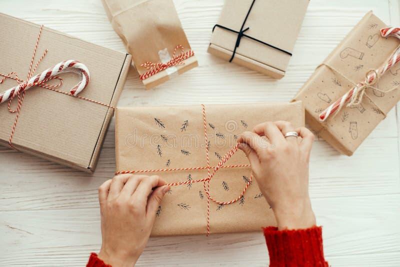 包裹与红色ro的红色毛线衣的妇女时髦的圣诞节礼物 免版税库存照片