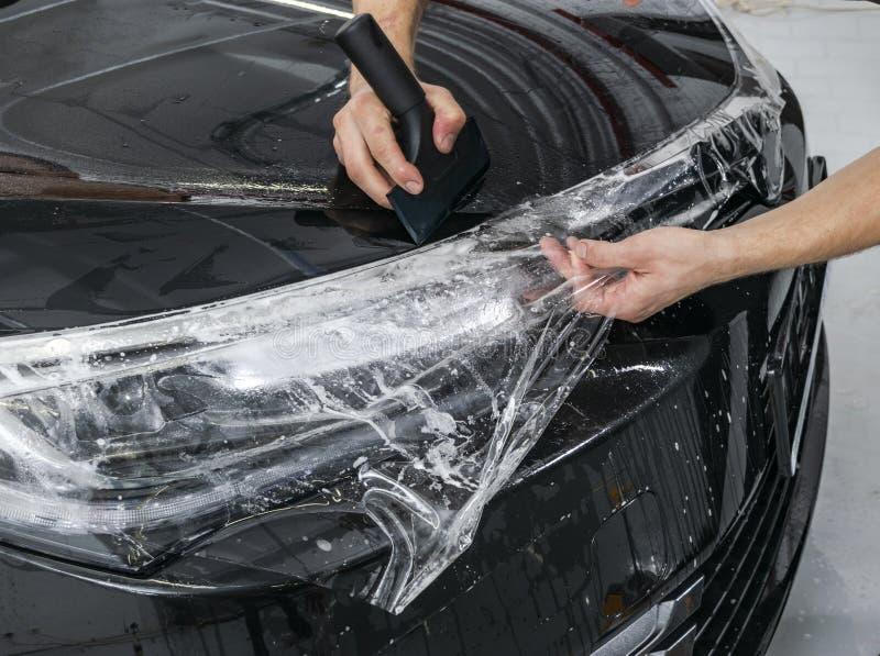 包裹专家的汽车把乙烯基箔或影片放在汽车上 保护胶卷 应用与工具的保护胶卷为工作 汽车de 免版税库存图片