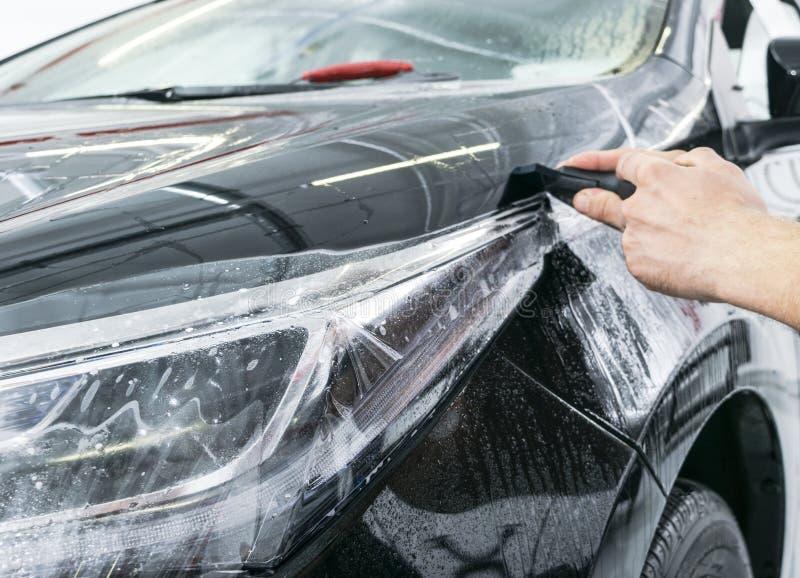 包裹专家的汽车把乙烯基箔或影片放在汽车上 保护胶卷 应用与工具的保护胶卷为工作 汽车de 免版税图库摄影