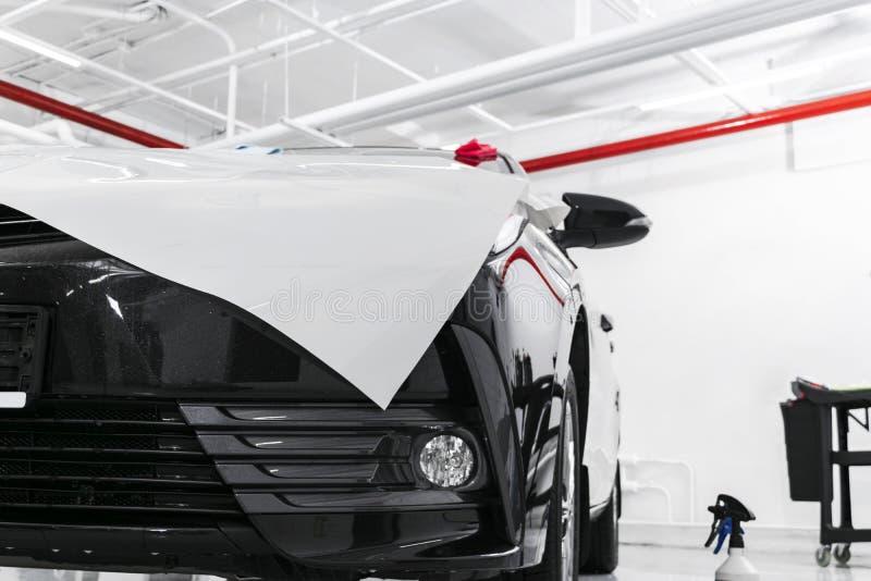 包裹专家的汽车把乙烯基箔或影片放在汽车上 在汽车的保护胶卷 适用于保护胶卷汽车与 免版税图库摄影