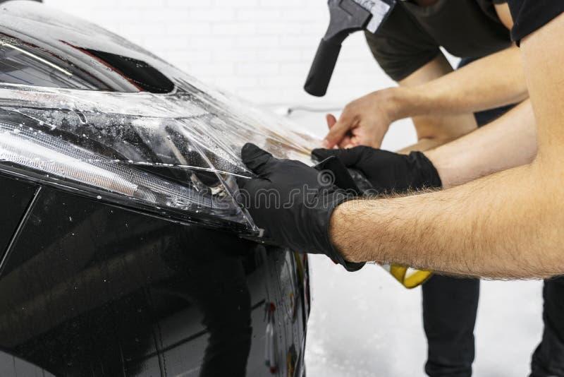 包裹专家的汽车把乙烯基箔或影片放在汽车上 在汽车的保护胶卷 适用于保护胶卷汽车与 免版税库存图片
