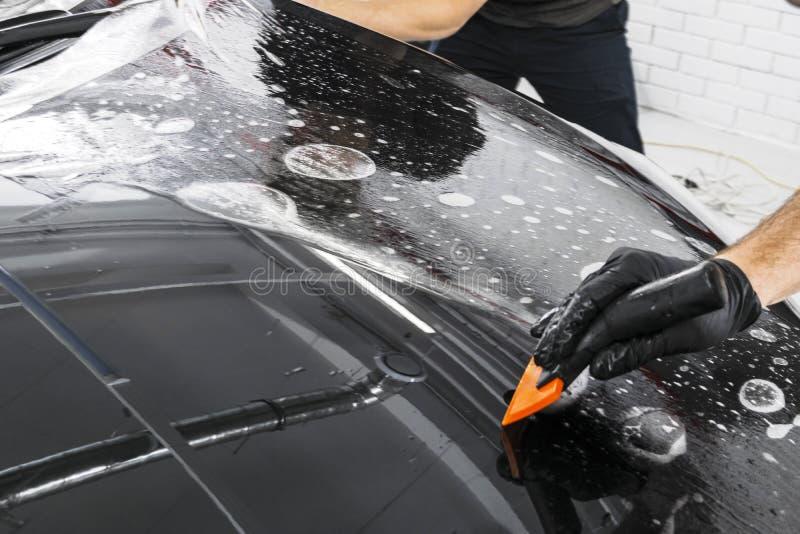 包裹专家的汽车把乙烯基箔或影片放在汽车上 在汽车的保护胶卷 适用于保护胶卷汽车与 库存图片