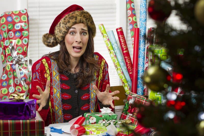 包裹圣诞节礼物的妇女,看起来挫败 免版税库存照片