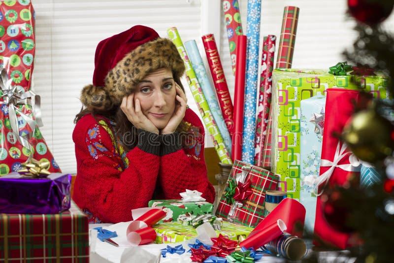 包裹圣诞节礼物的妇女,看起来用尽 免版税库存照片