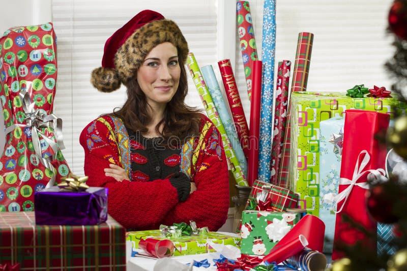 包裹圣诞节礼物的妇女,看起来满意 免版税库存照片
